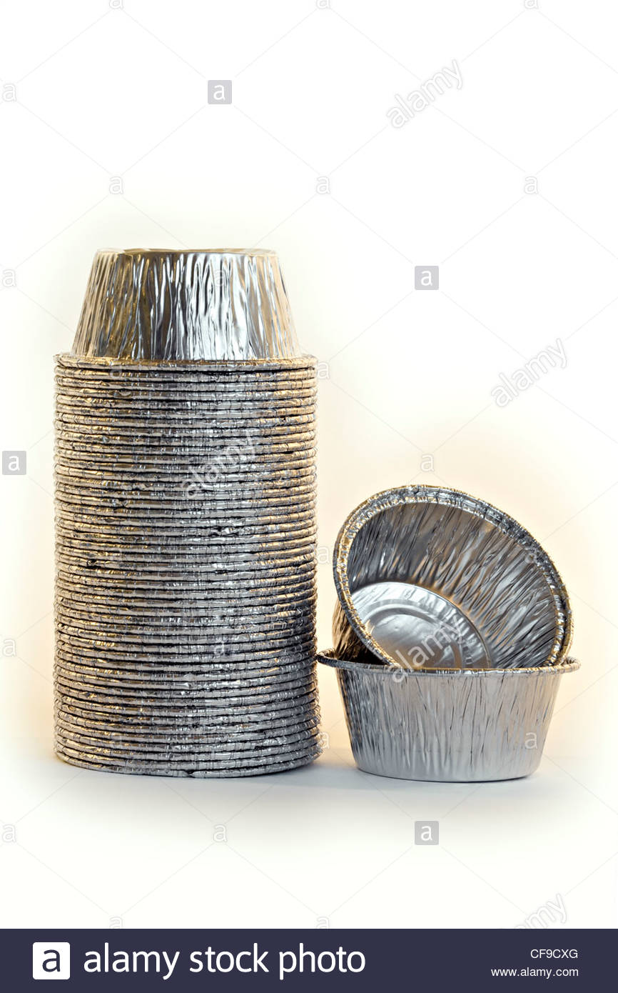 Close-up of stack of cup cake tins on white background - Stock Image