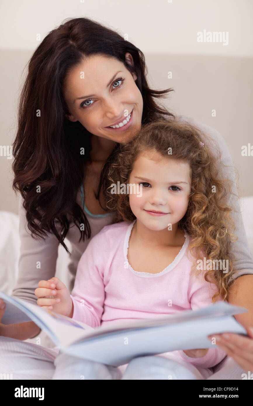 Smiling mother reading a bedtime story with her little daughter - Stock Image
