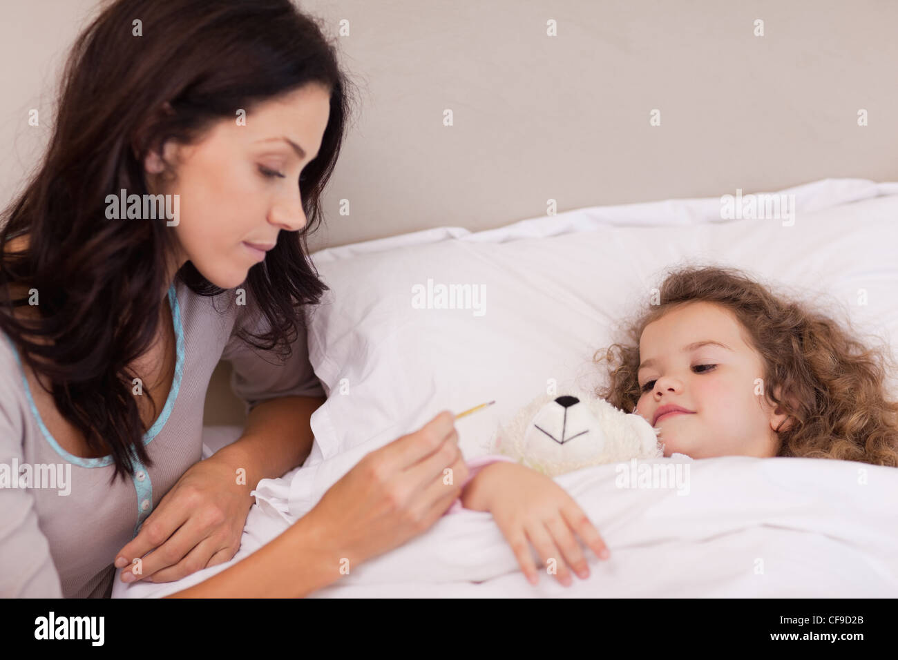 Mother taking her daughters temperature - Stock Image