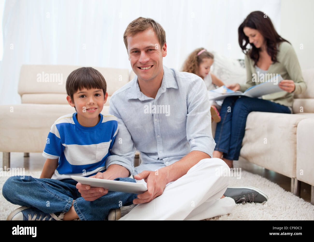 Family spending free time in the living room - Stock Image
