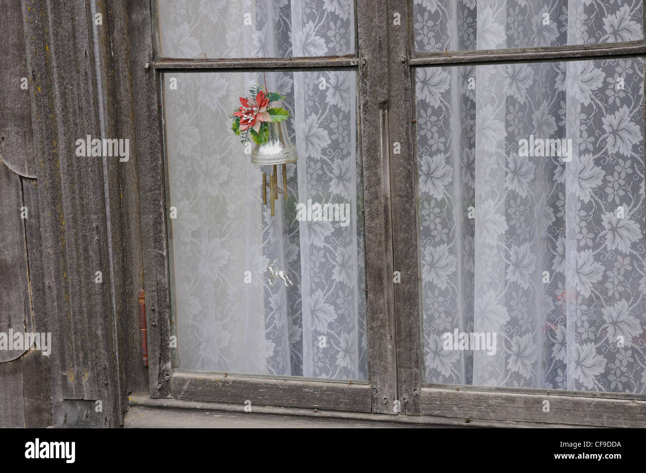 Christmas decorations in wood framed window with floral patterned net curtains. - Stock Image