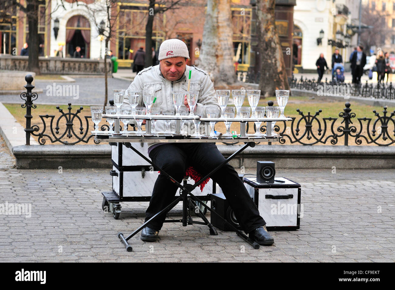 street musician in Budapest entertaining the crowds by playing on wine glasses filled with varied levels of water - Stock Image