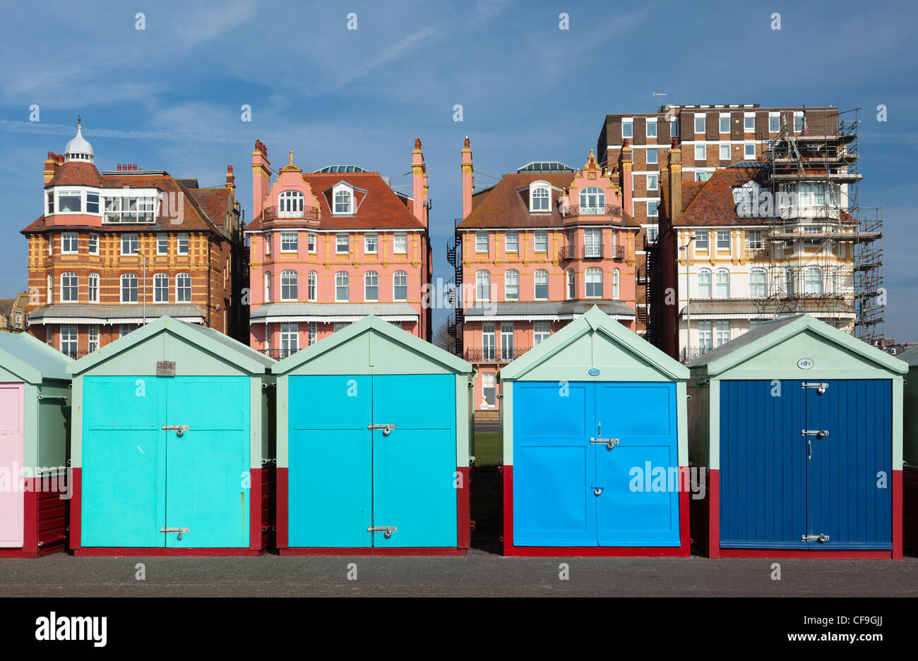 Brightly coloured beach huts on Brighton & Hove seafront with period buildings behind Stock Photo