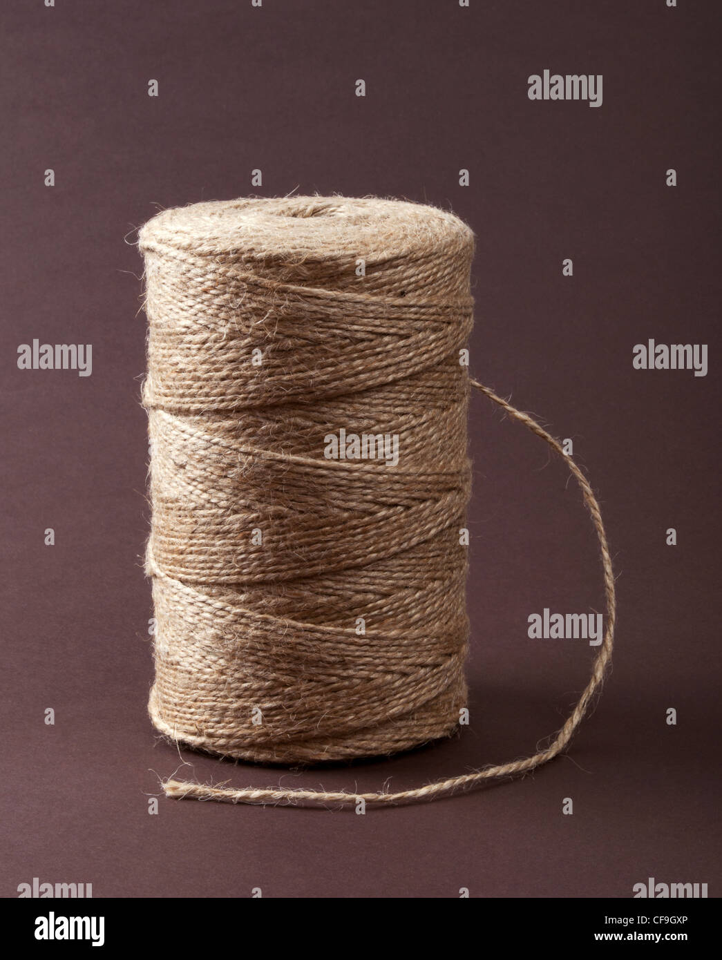 Roll of sisal rope on dark brown background - Stock Image