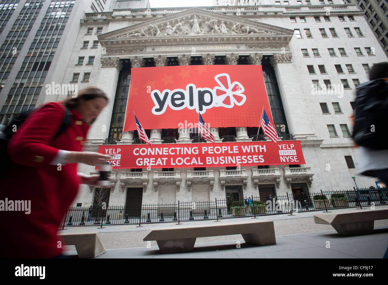 The facade of the New York Stock Exchange decorated in honor of the initial public offering of Yelp - Stock Image