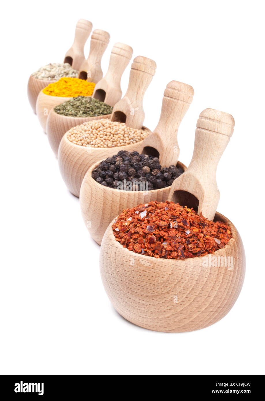 Row of wooden bowls with spices in them. Diminishing perspective - Stock Image