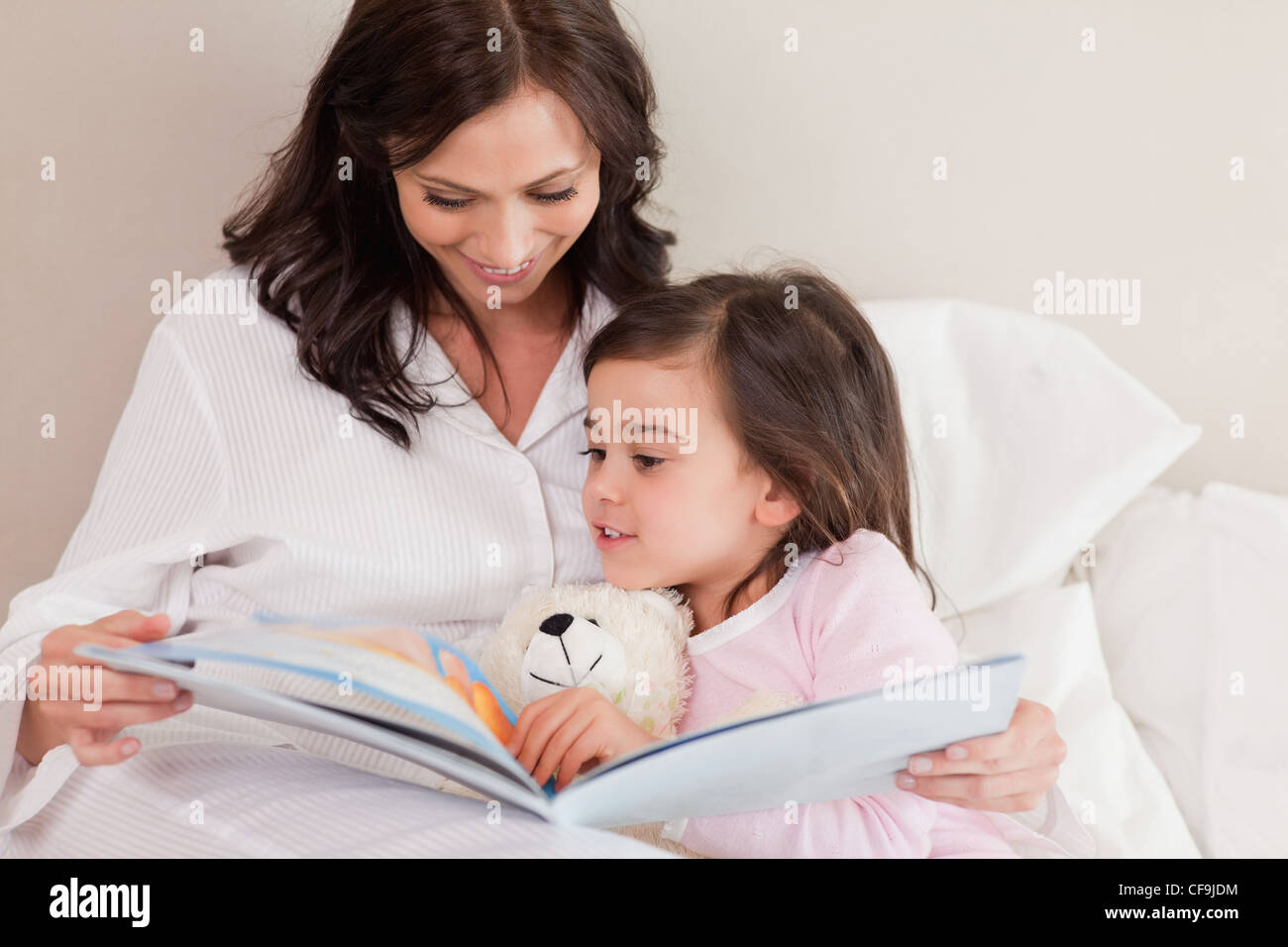 Mother reading a story to her daughter - Stock Image