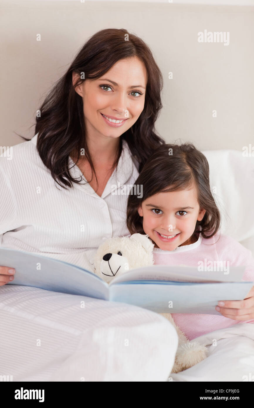 Portrait of a happy mother reading a story to her daughter - Stock Image