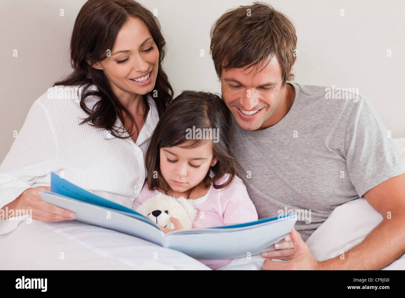Happy parents reading a story to their daughter Stock Photo