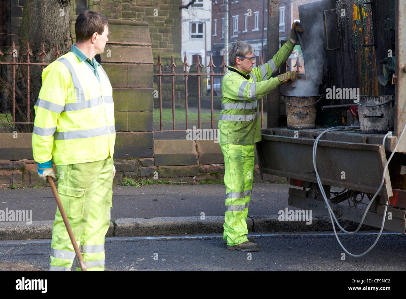 road construction workers installing hot applied high friction road surfacing Belfast Northern Ireland UK - Stock Image