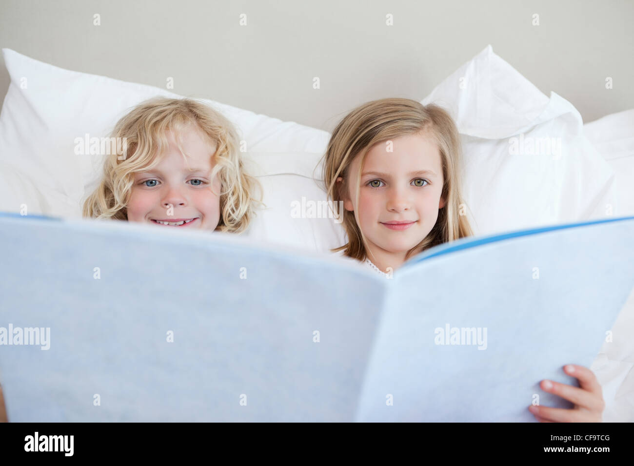 Brother and sister reading bedtime story - Stock Image