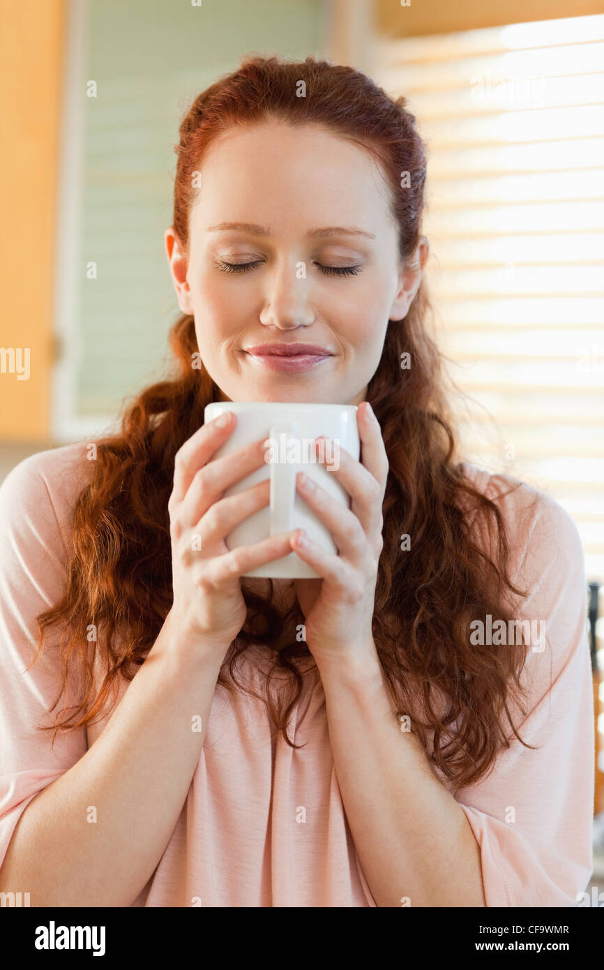 Joyful woman holding a cup of coffee - Stock Image