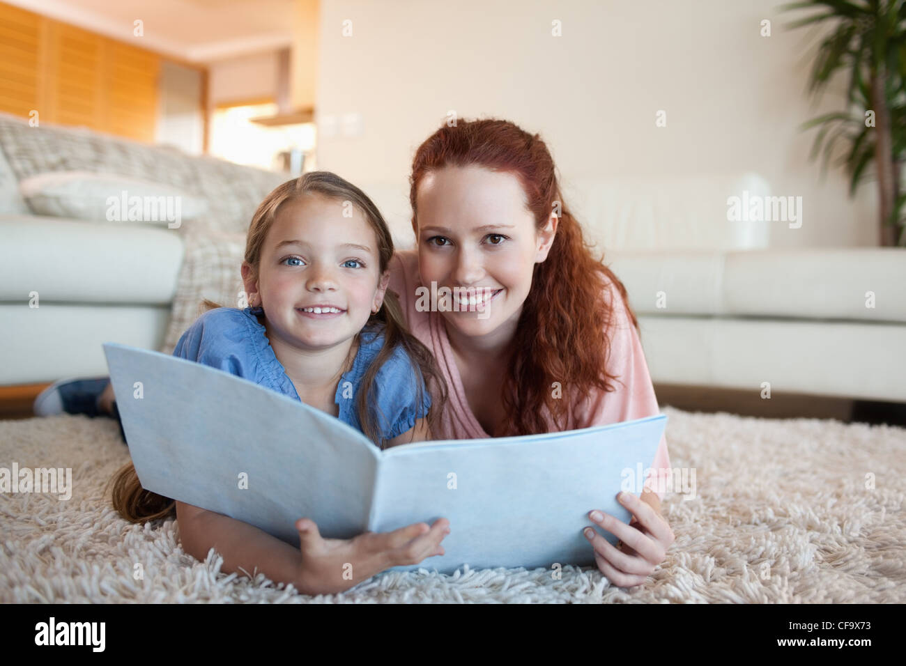 Mother and daughter looking at periodical - Stock Image