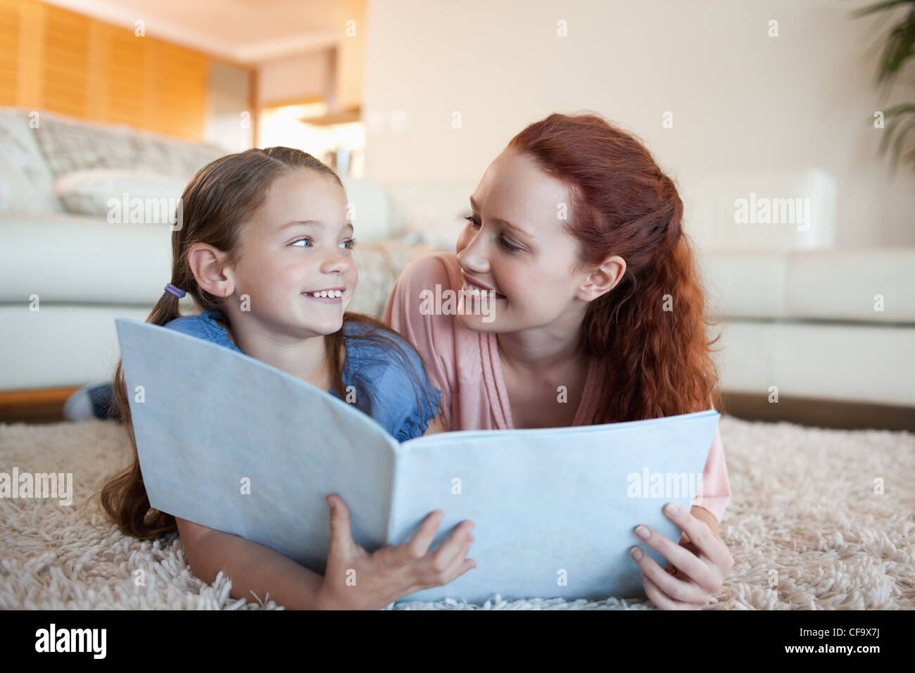Mother and daughter with periodical on the floor - Stock Image