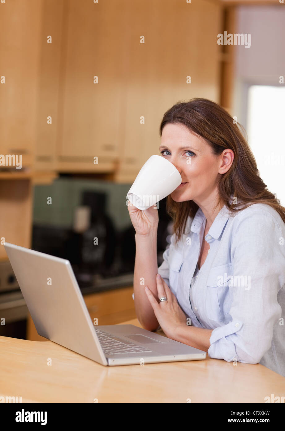Woman taking a sip of coffee next to laptop - Stock Image