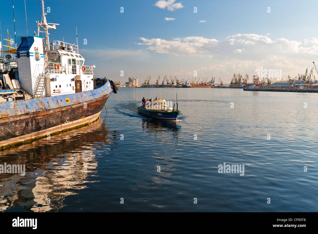 Small boat is passing by a docked towboat. - Stock Image