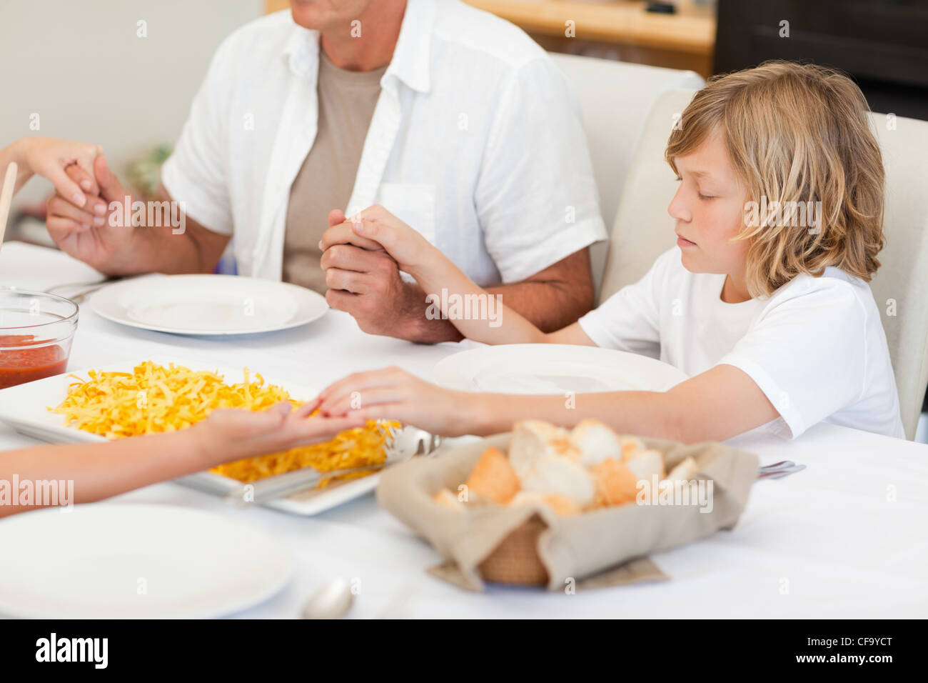 Family saying a prayer before dinner Stock Photo