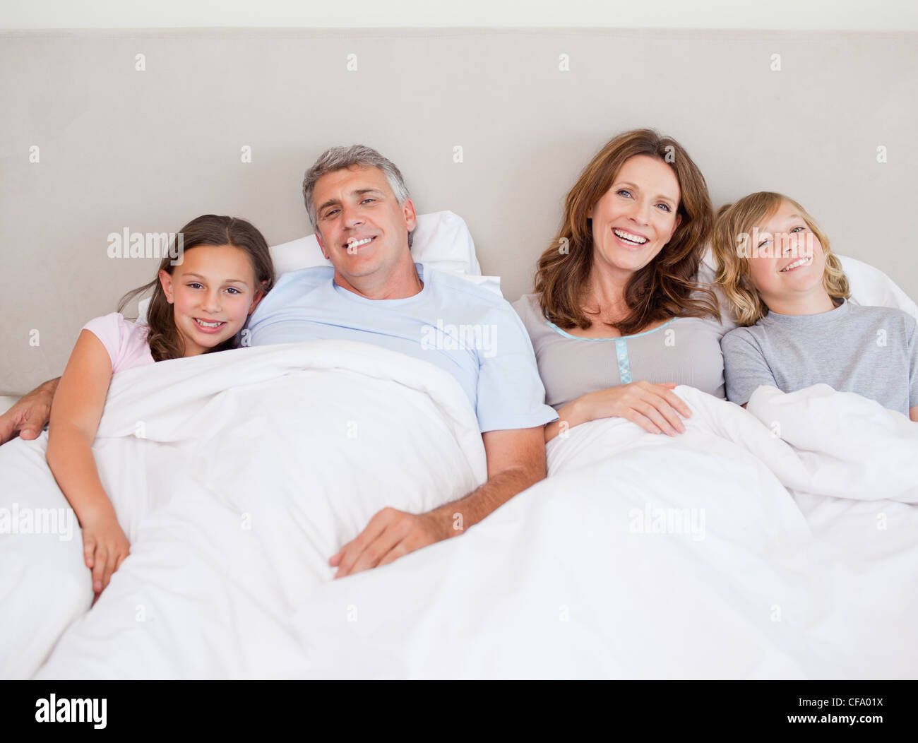 Happy family about to take a nap - Stock Image