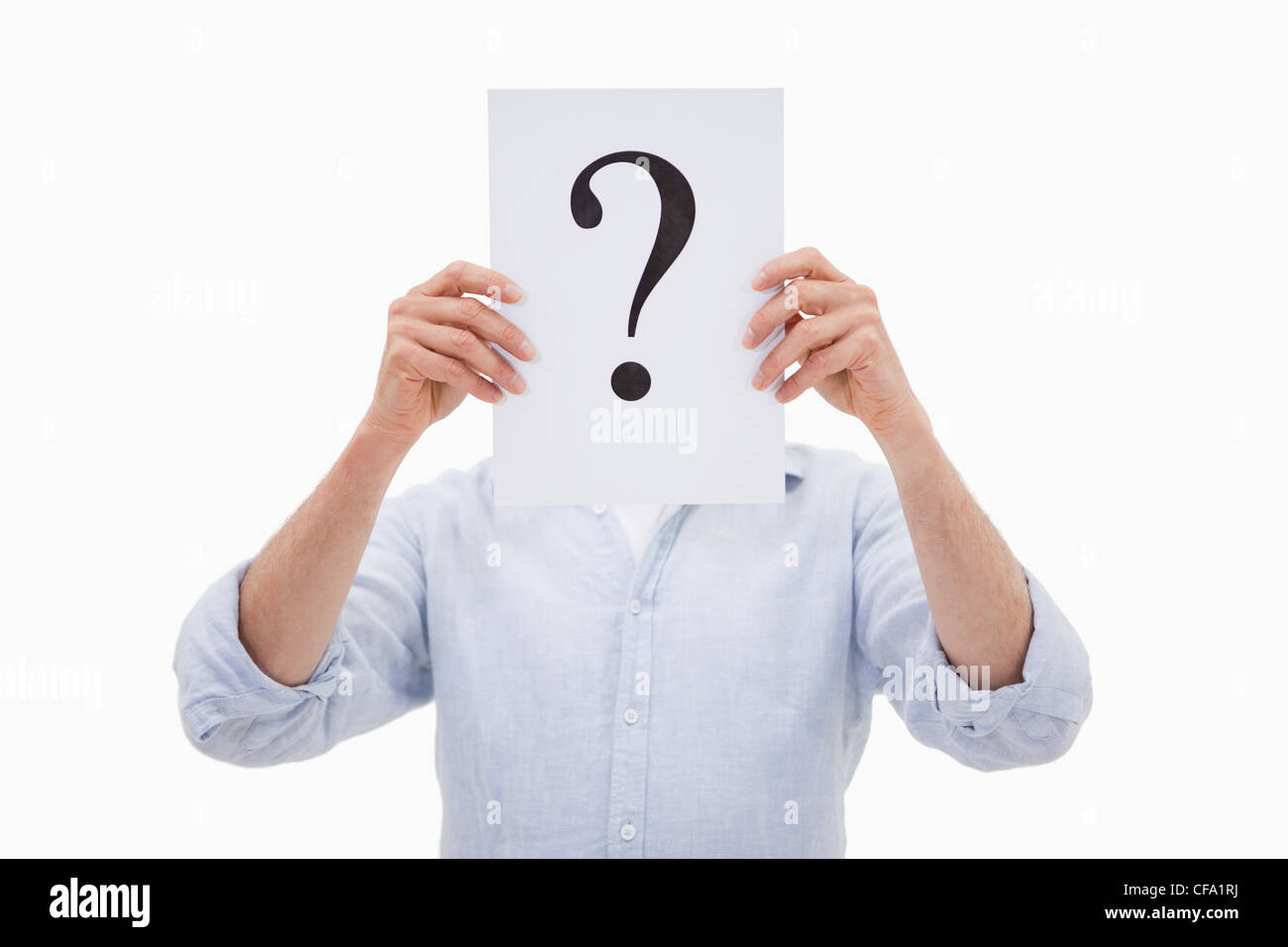 Portrait of a man hiding his face behind a question mark - Stock Image