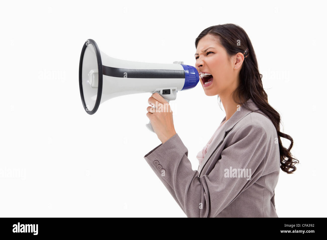 Side view of angry businesswoman shouting through megaphone Stock Photo