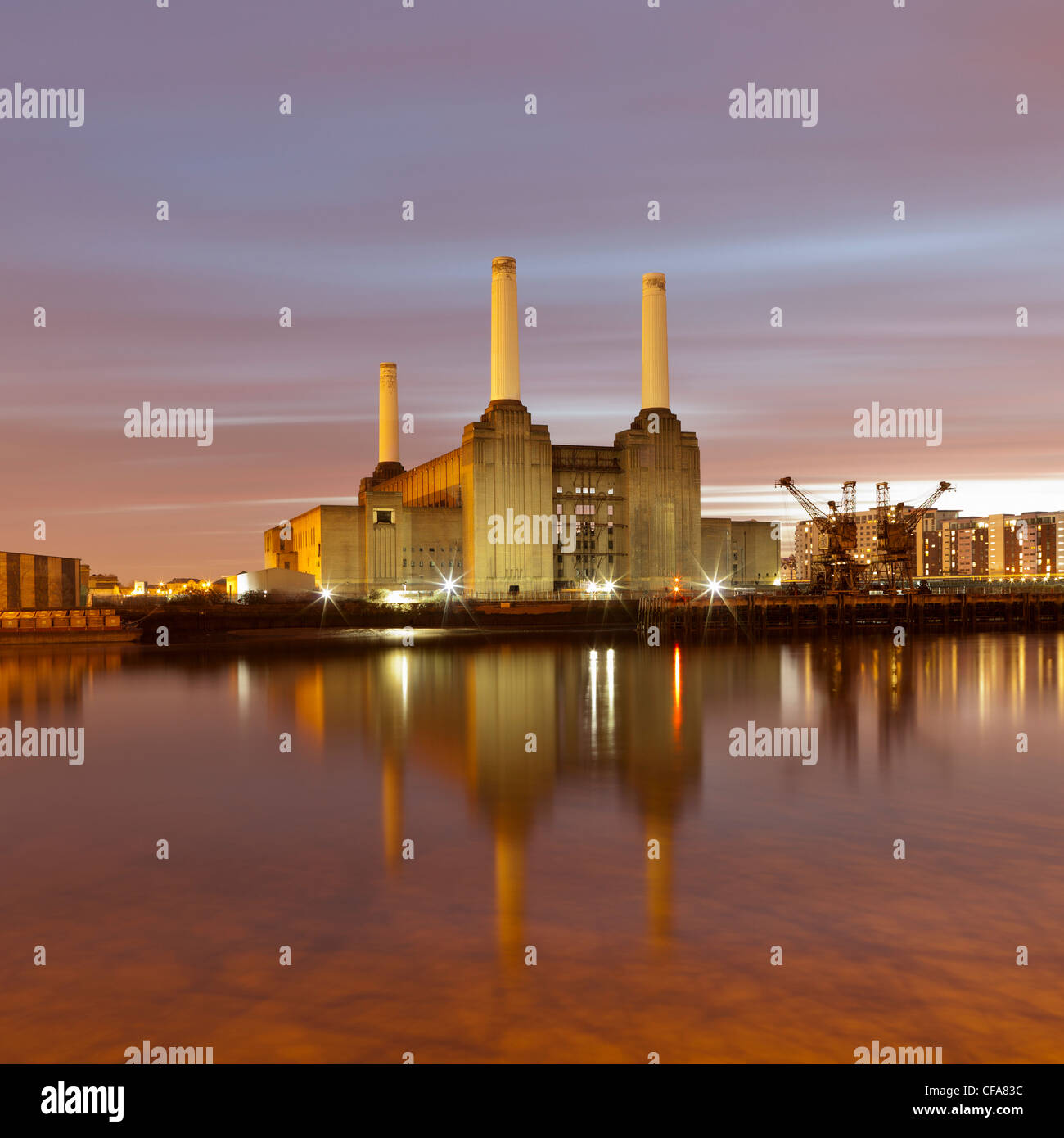 Factory on waterfront lit up at night - Stock Image