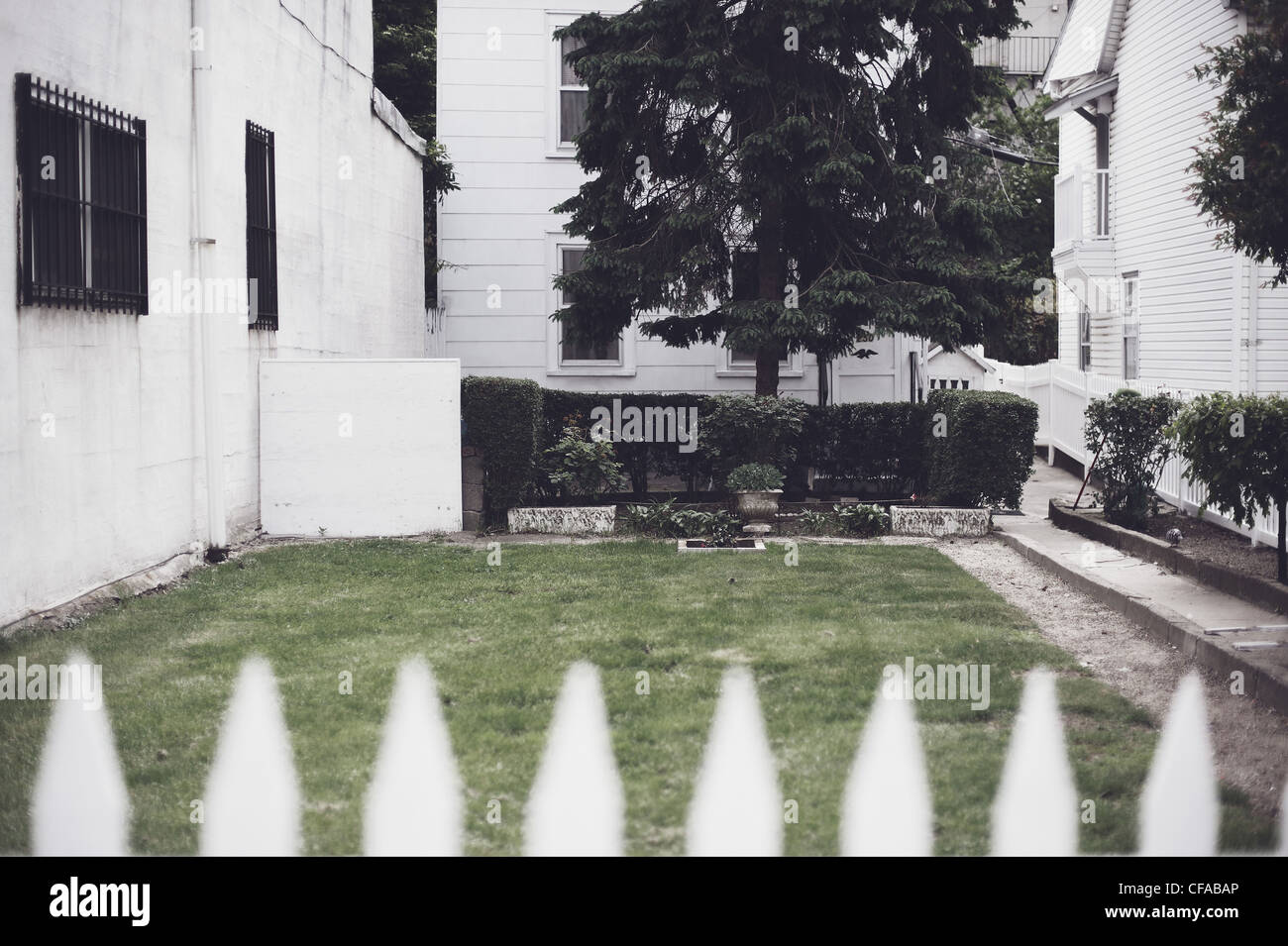 White picket fence in front yard - Stock Image