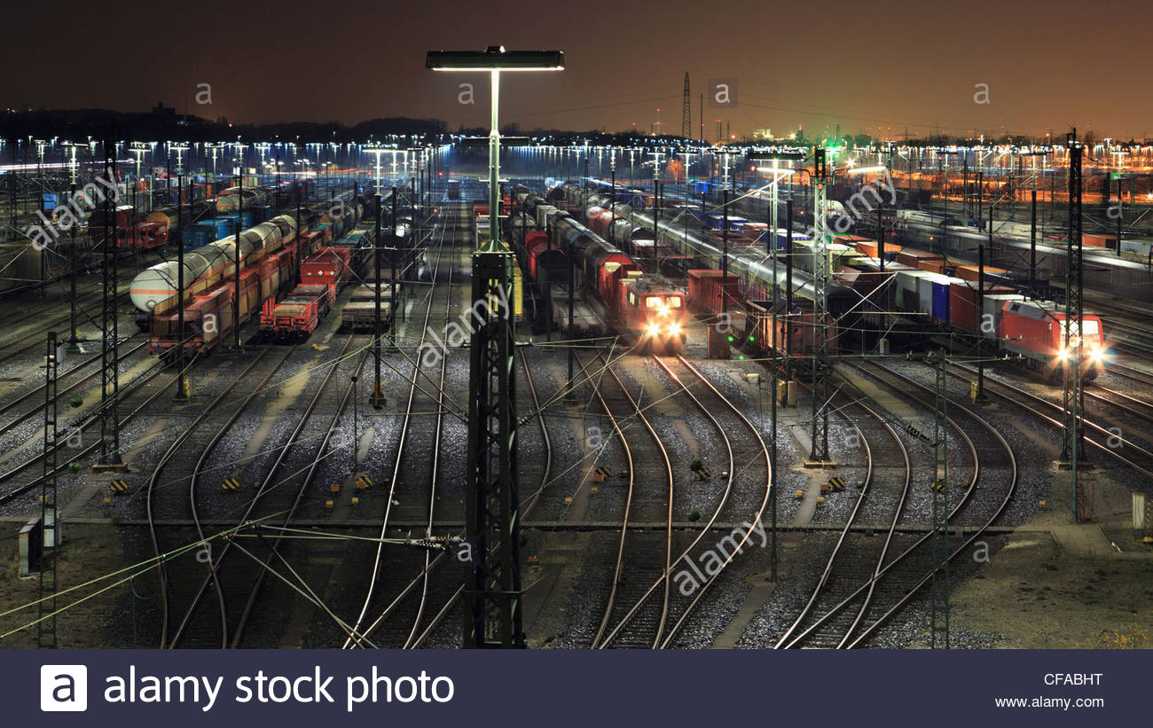 Train yard lit up at night - Stock Image