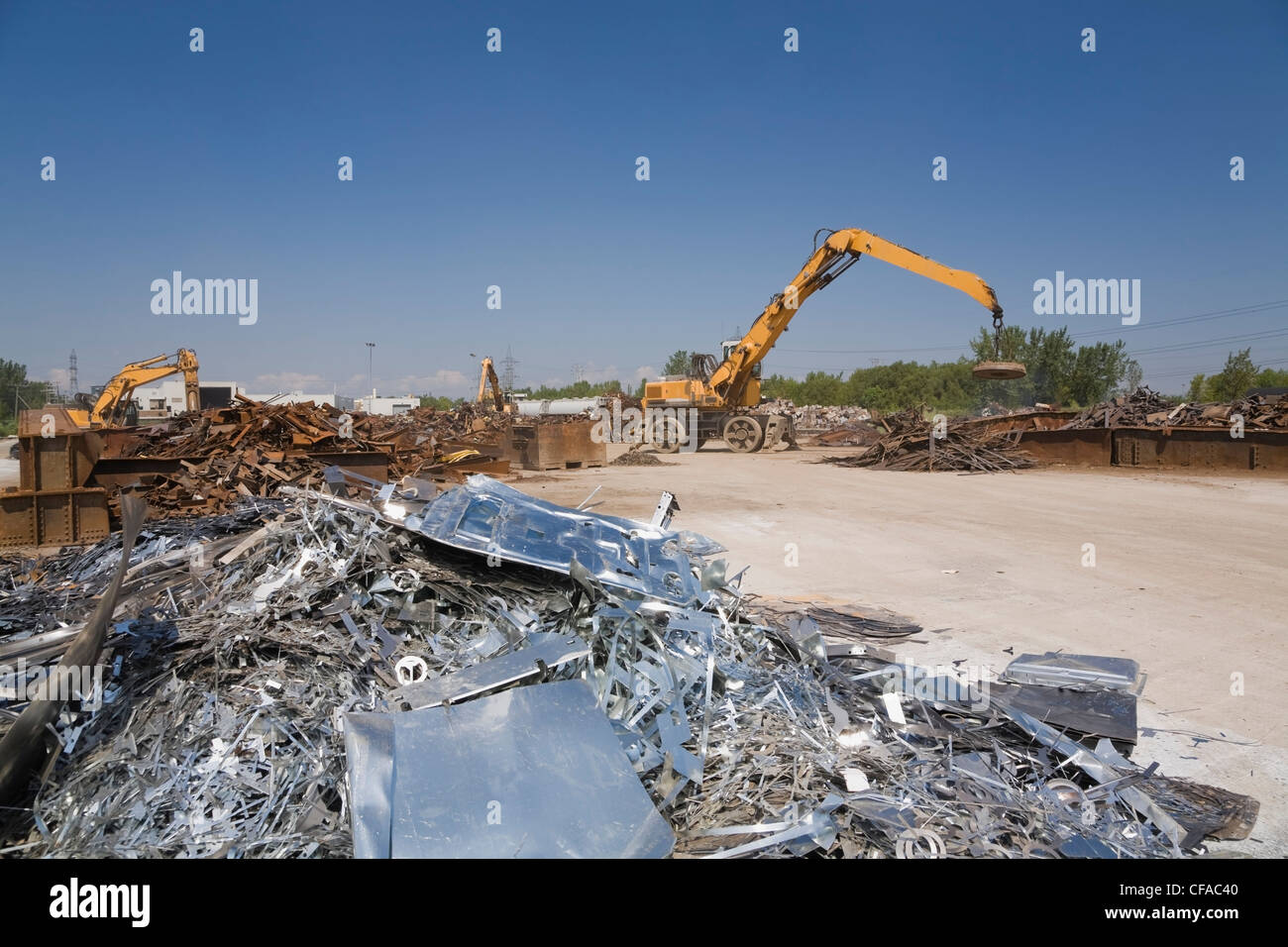Material handler fitted with a magnet moving a pile of ferous metal at a scrap metal recycling yard, Quebec, Canada. - Stock Image