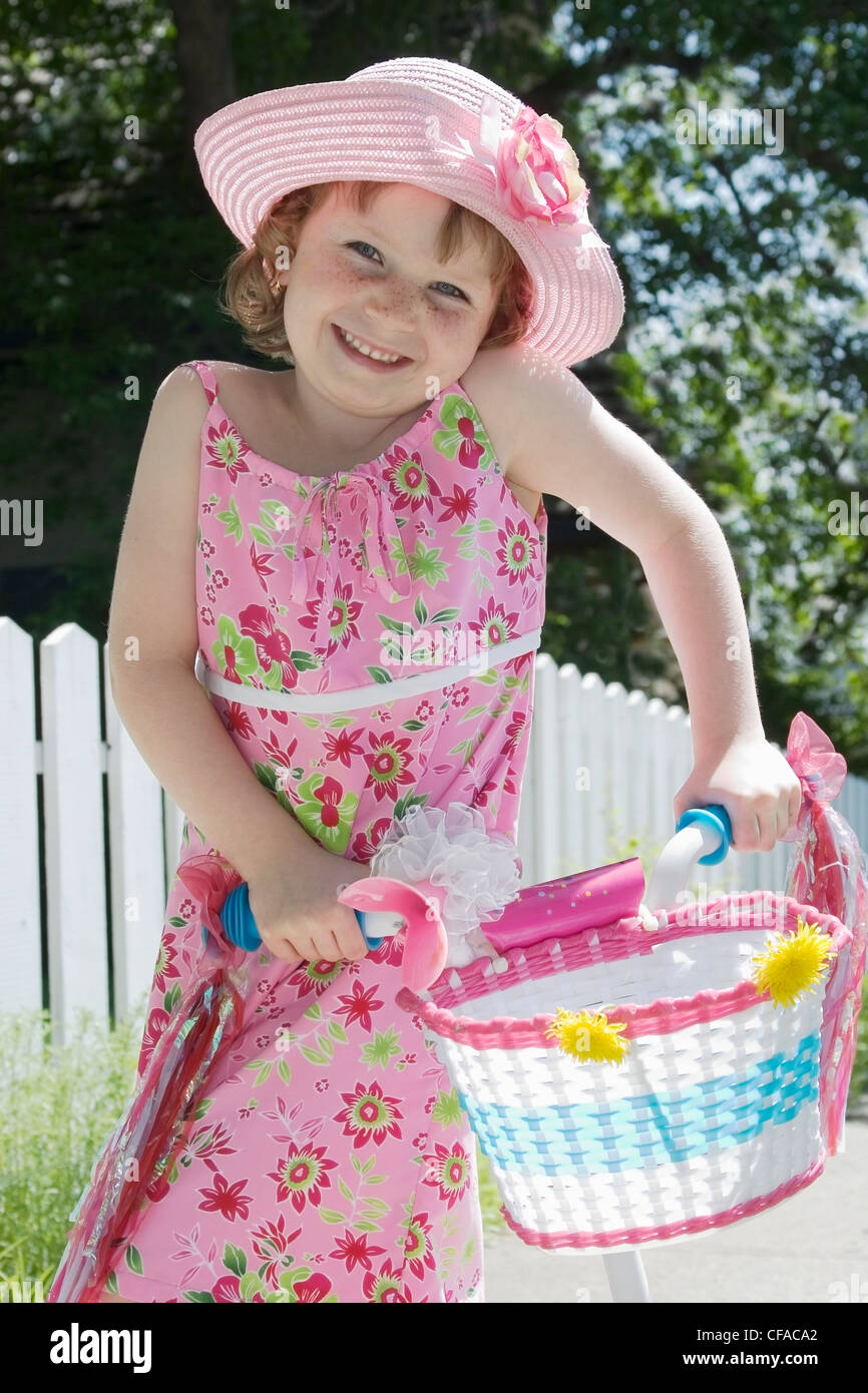 Girl with sundress and hat standing in front of picket fence with bicycle, Canada. - Stock Image