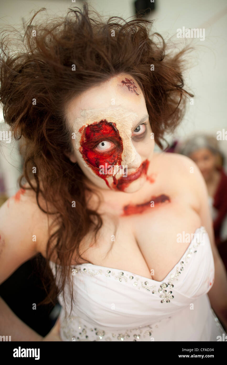 a young woman wearing full prosthetic makeup  taking part in a Zombie bride 'trash the wedding dress' event - Stock Image