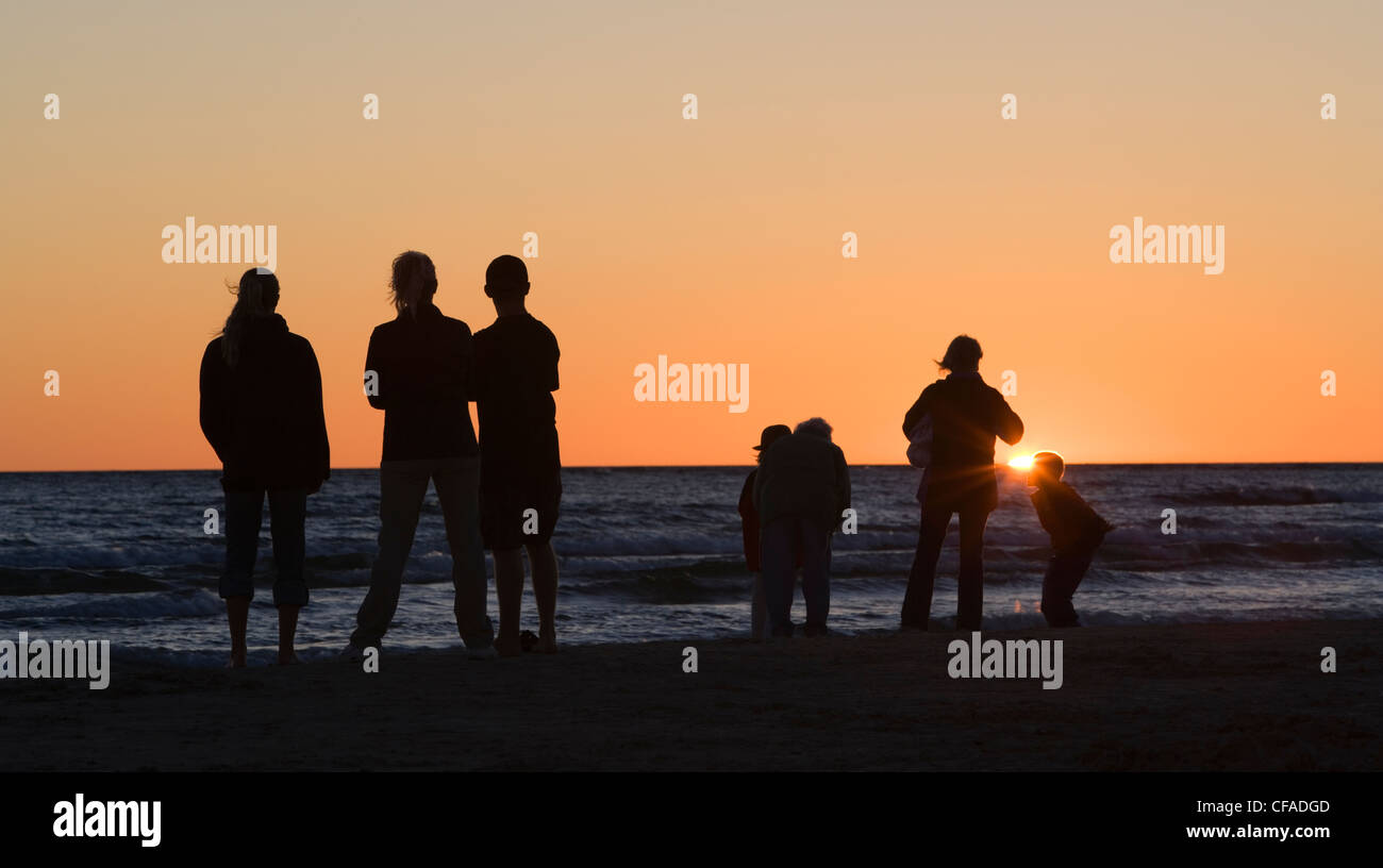 A family watches the sunset over Lake Huron at Sauble Beach, Ontario, Canada. - Stock Image