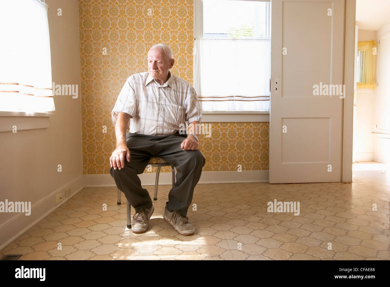 senior citizen (70-80 years old) sitting on chair in vacant house ...