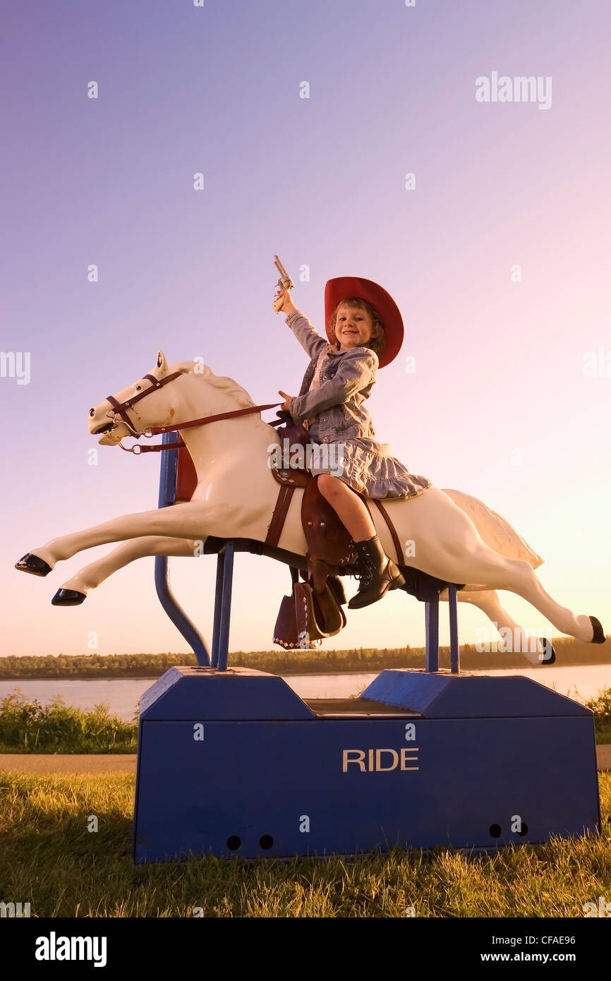 5 year old girl dressed in western attire sitting on amusement pony ride, Canada. - Stock Image