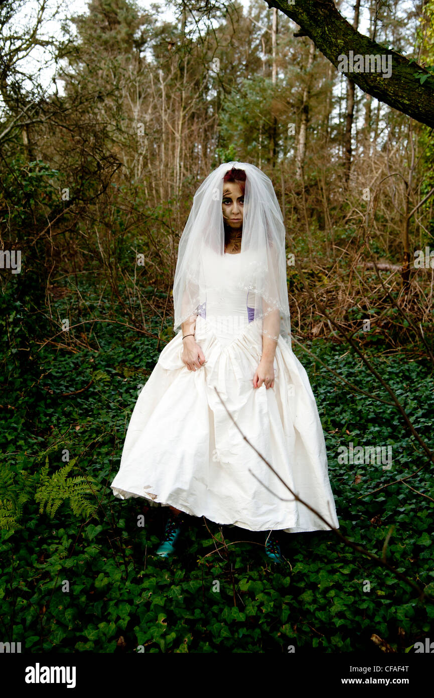 A young woman dressed as a bride alone in the woods in a 'trash the dress' photoshoot - Stock Image