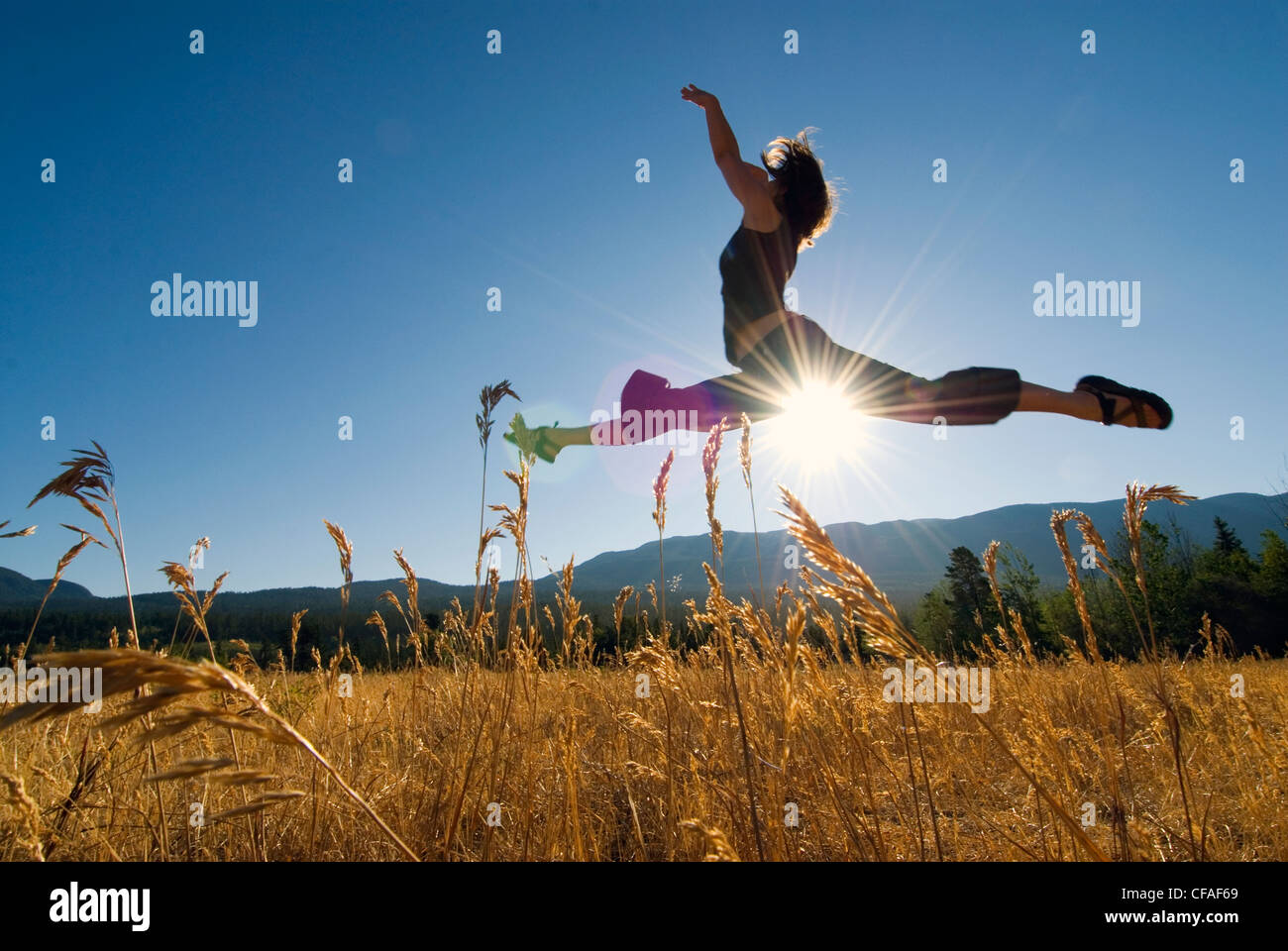 Female dancer in a grassy field with sun shining, Tatlayoko Lake, British Columbia, Canada. - Stock Image