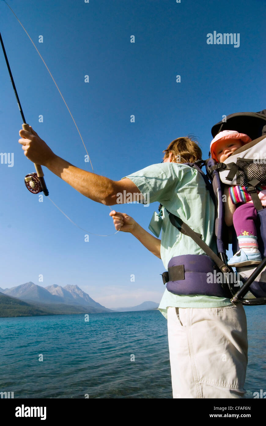 Fisherman father with daughter in child-carrier backpack, fly-fishing for trout, Tatlayoko Lake, British Columbia, - Stock Image