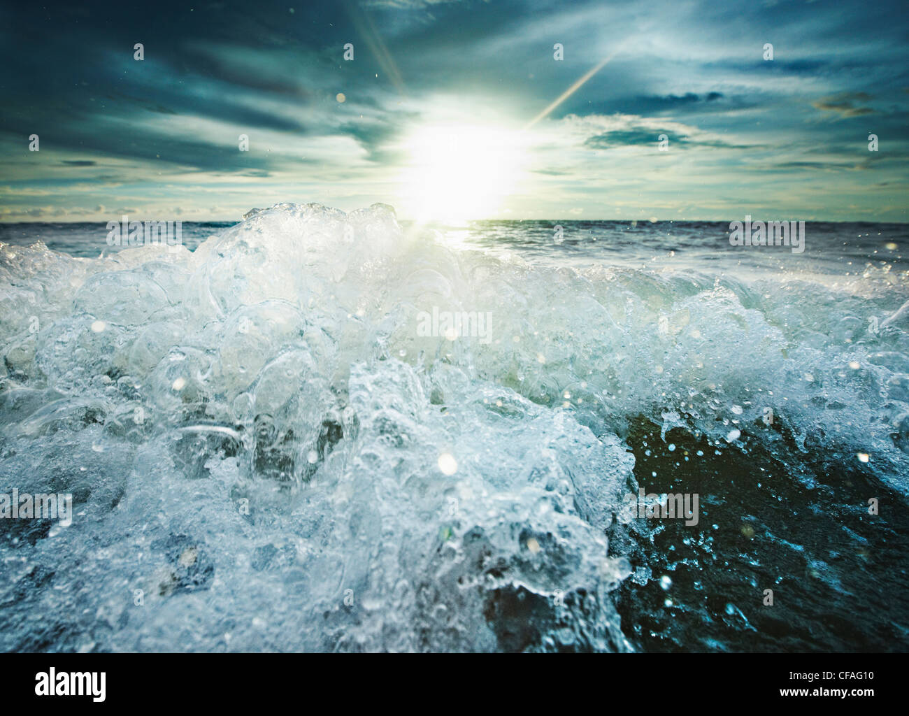 Sun shining over rocky waves - Stock Image