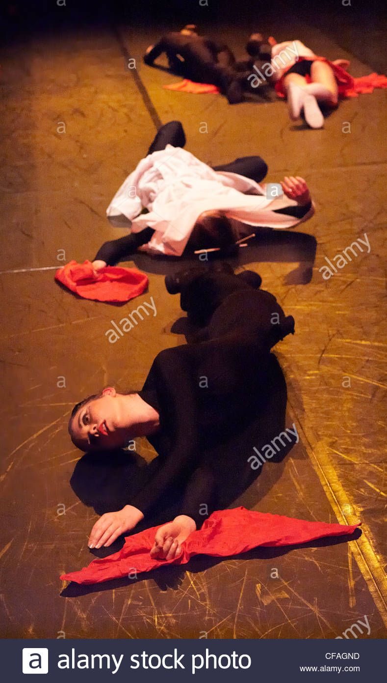Female dancers lying onstage, playing dead during a Tarantino-inspired performance at a community arts centre. Red, - Stock Image