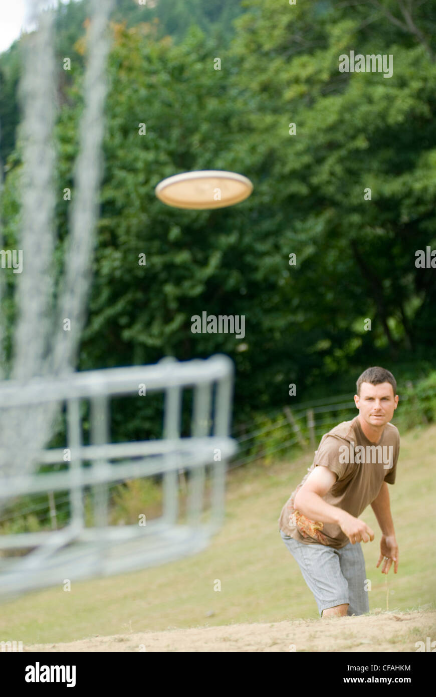 Man putting with frisbee while playing a round of disc golf, near Victoria, British Columbia, Canada - Stock Image