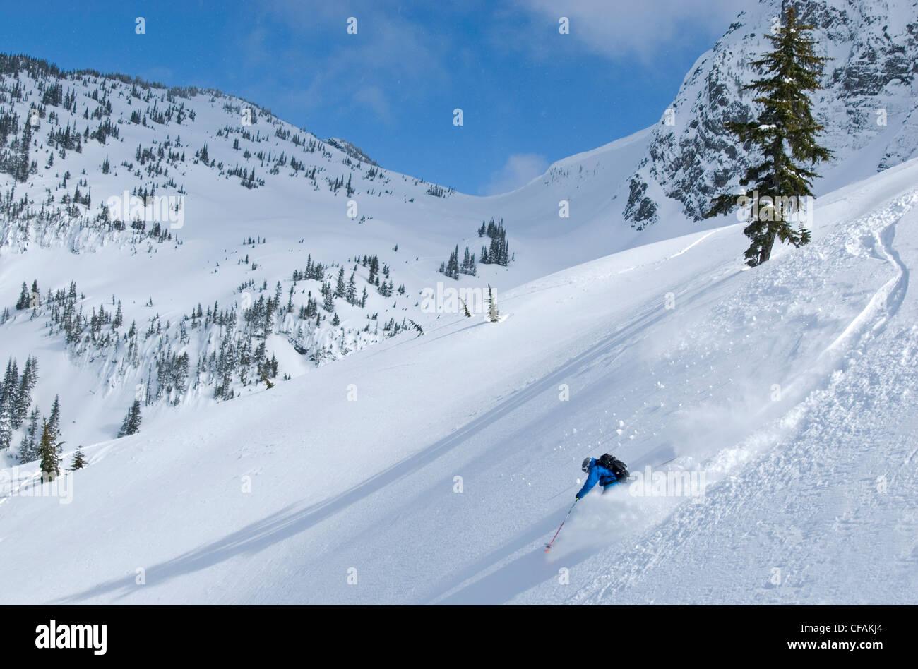 Skier hitting the powder below Nak Peak in Thar Basin Cascade Mountains, British Columbia, Canada. - Stock Image