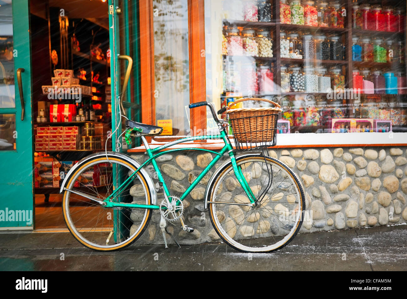 Cruiser bicycle with basket parked outside a Candy Store during a snowfall. Banff, Alberta, Canada. - Stock Image