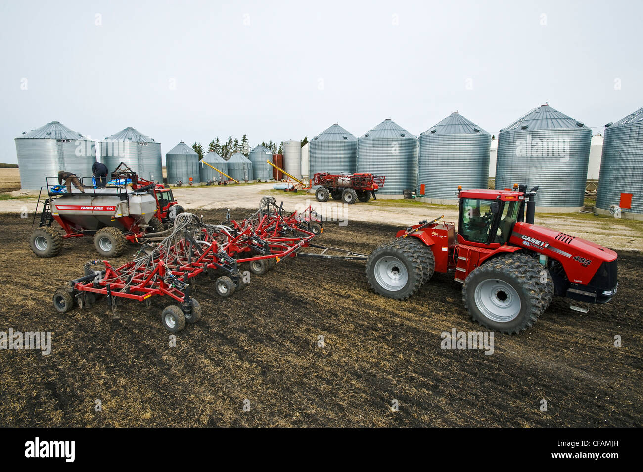 farmers loading a seeding tank next to farmyard, near Dugald, Manitoba, Canada - Stock Image