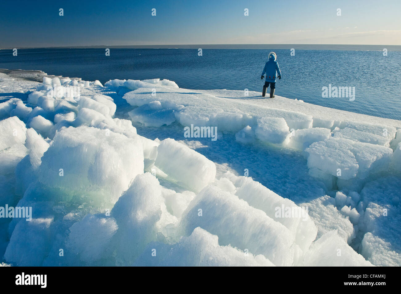 a man looks out over melting ice, along Lake Winnipeg, Manitoba, Canada - Stock Image