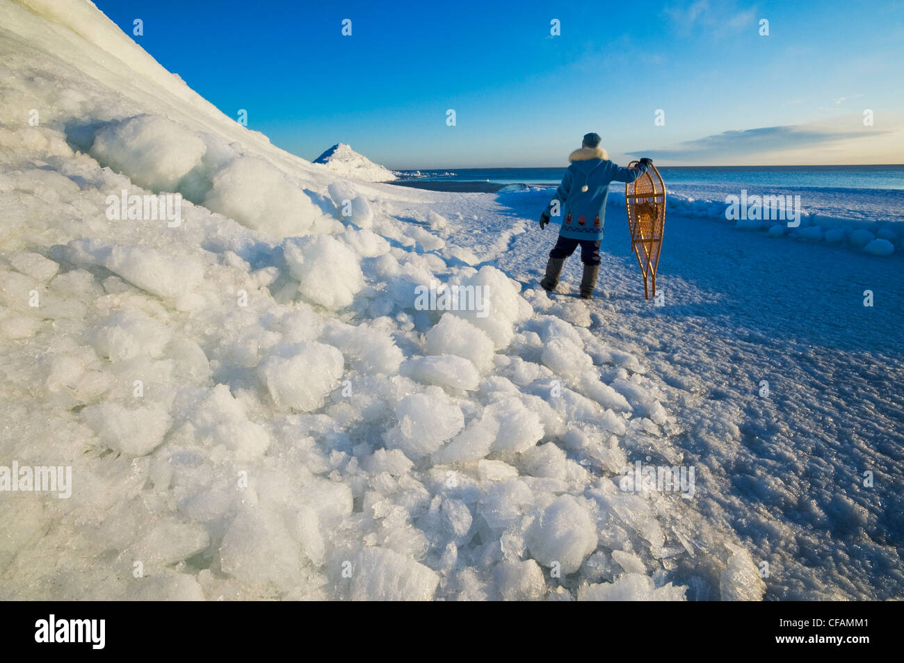 a man with snowshoes looks out over washed up ice piles, along Lake Winnipeg, Manitoba, Canada - Stock Image