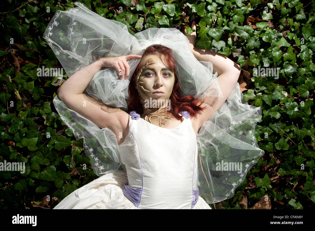 A young woman dressed as a bride lying in ivy alone in the woods in a 'trash the dress' photoshoot - Stock Image