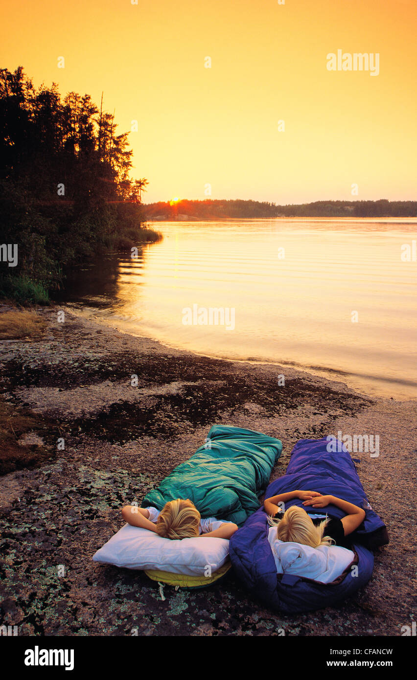 Two children in sleeping bags along shoreline of lake, Whiteshell Provincial Park, Manitoba, Canada - Stock Image
