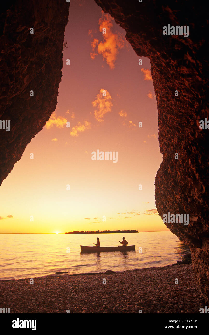 Silhouette of a couple in the distance, canoeing Steep Rock along Lake Manitoba, Manitoba, Canada - Stock Image
