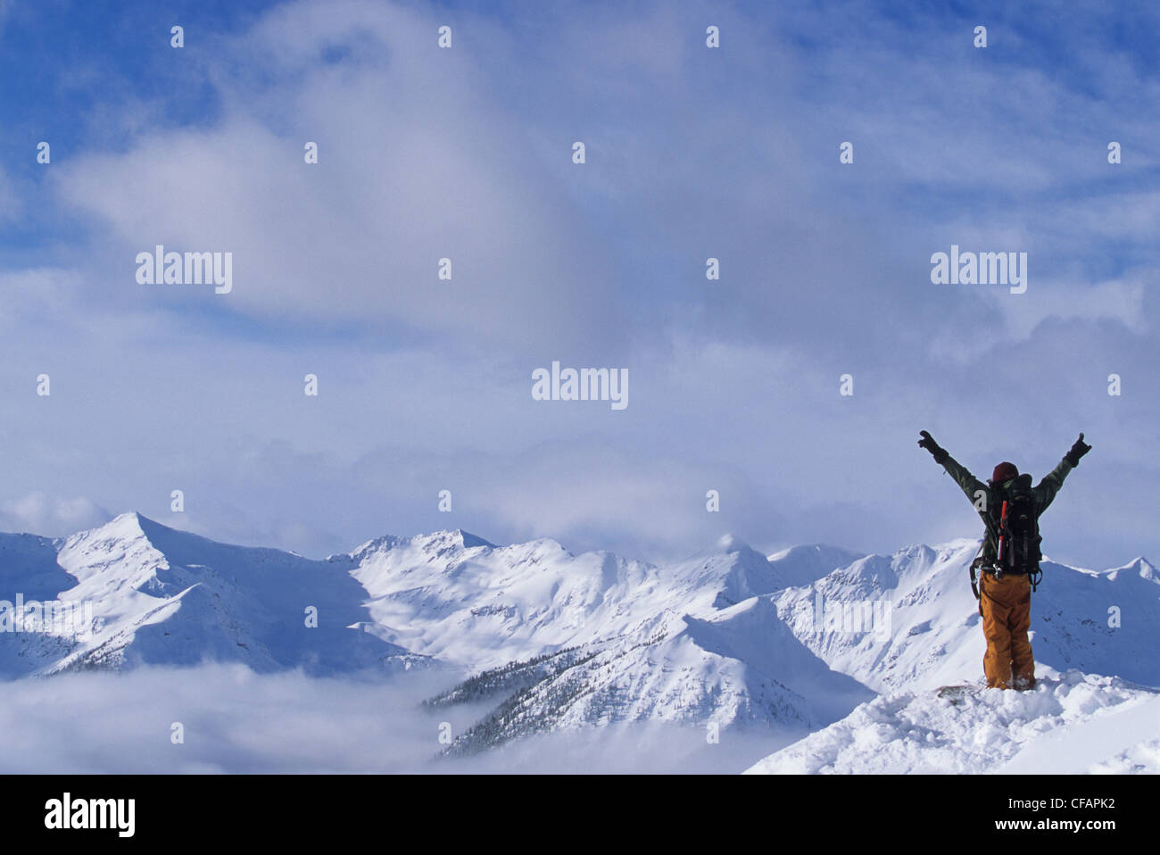 A skier enjoying the view of the snowy mountain peaks in the backcountry, Purcell Range, Golden, British Columbia, - Stock Image