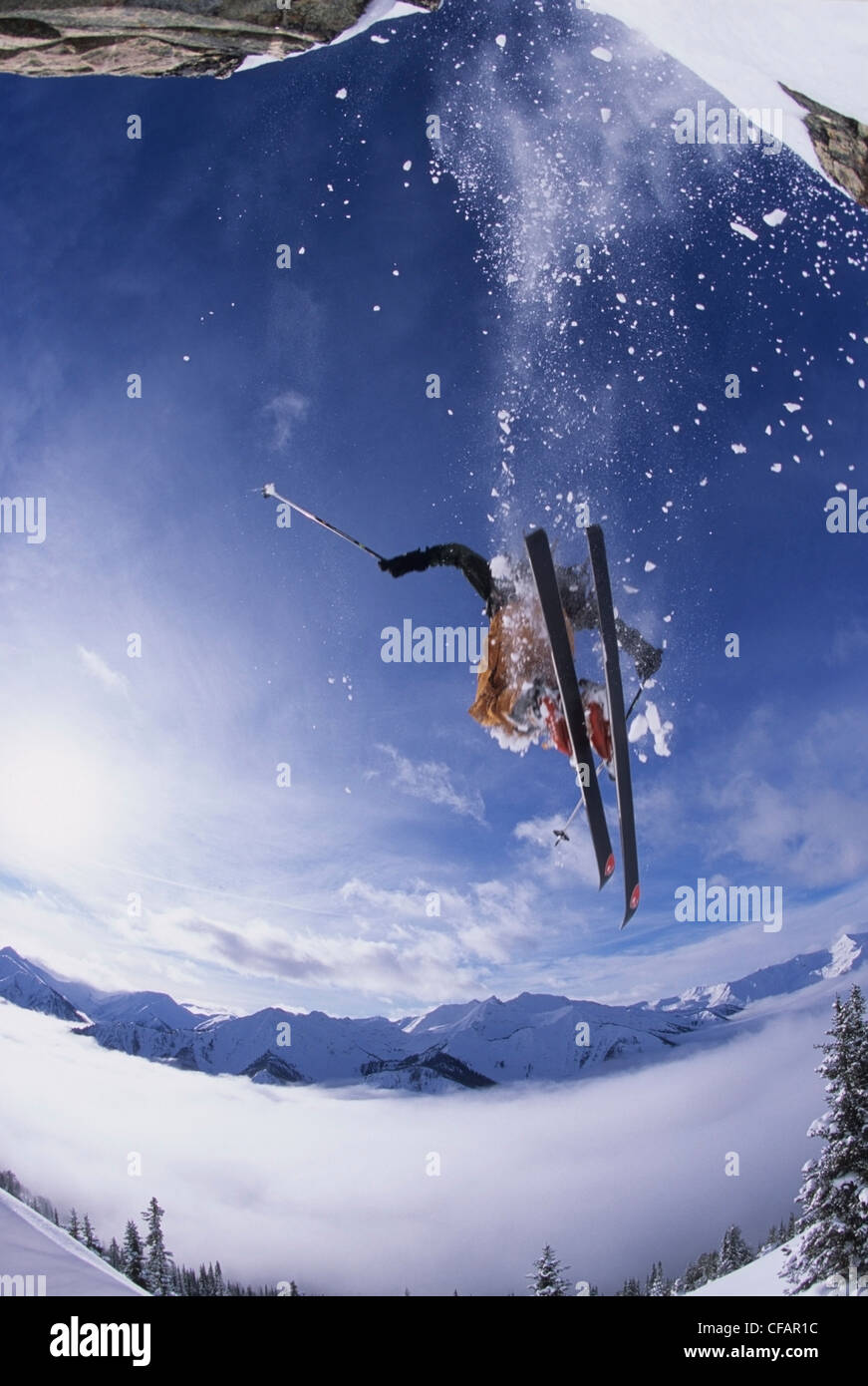 A skier catching some air after jumping a cliff in the backcountry of Kickinghorse Resort Area, Golden, British - Stock Image