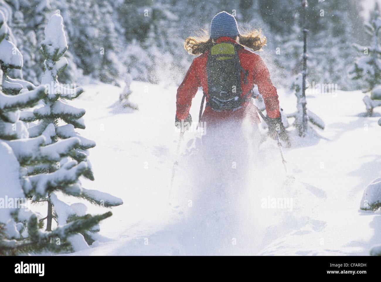 A young female snowshoer enjoying a winter morning run in Kananaskis Country, Alberta, Canada - Stock Image